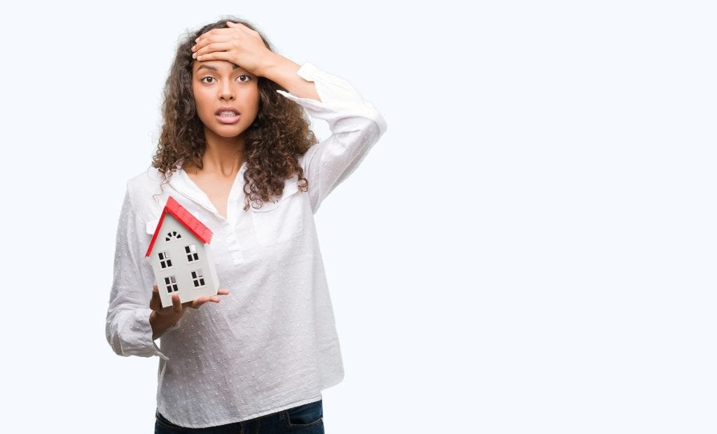 Woman doing facepalm while holding a mini-home model