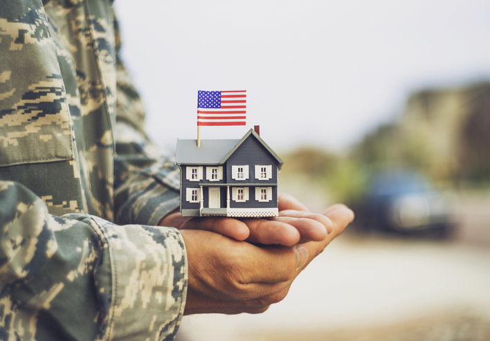Soldier holding a miniature house with an American flag