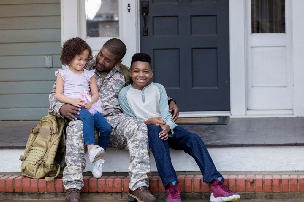 Militar dad and his kids happily sitting on a porch