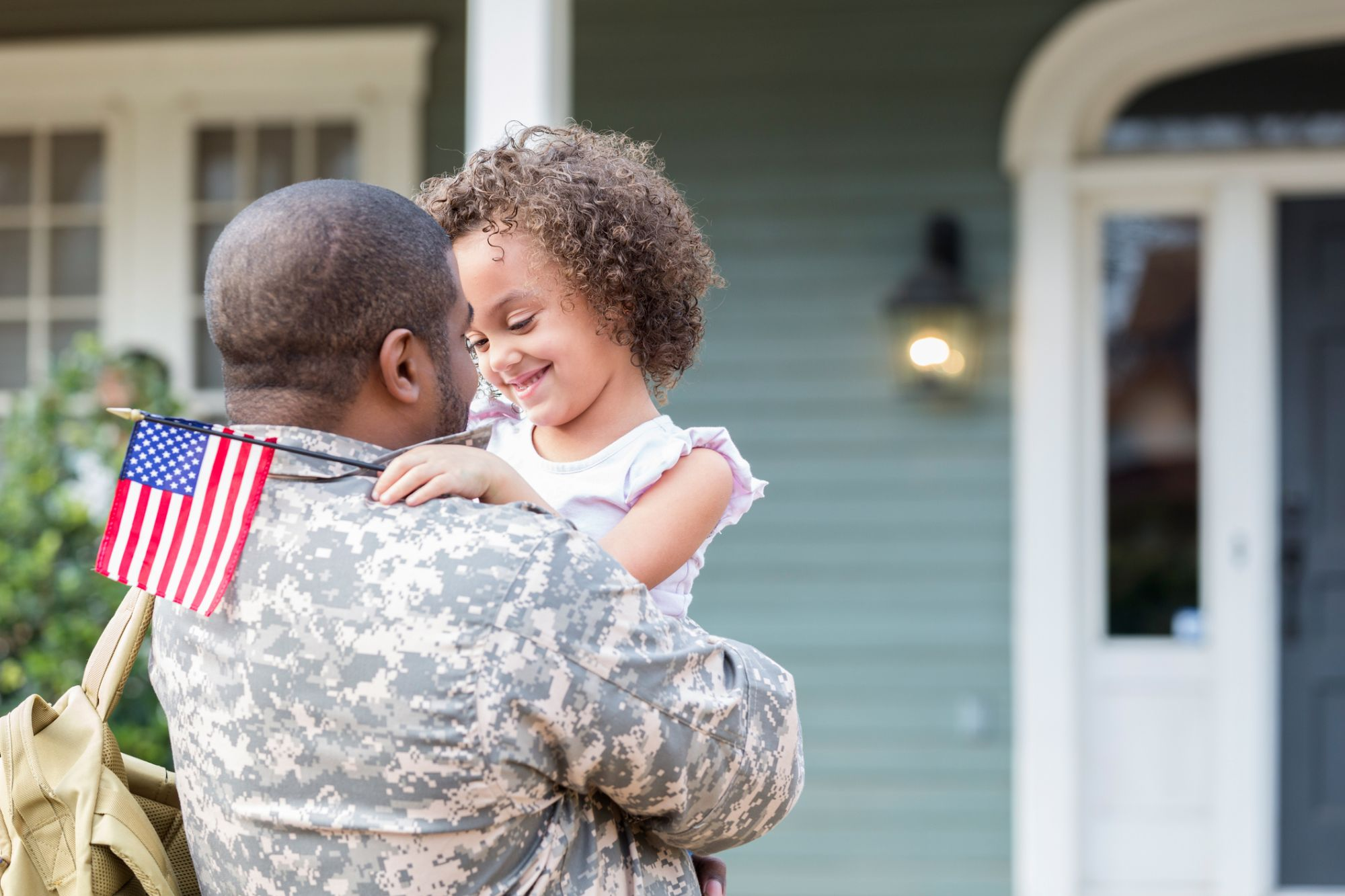 Young mixed race girl smiles while hugging her army dad. Her dad is home on leave.