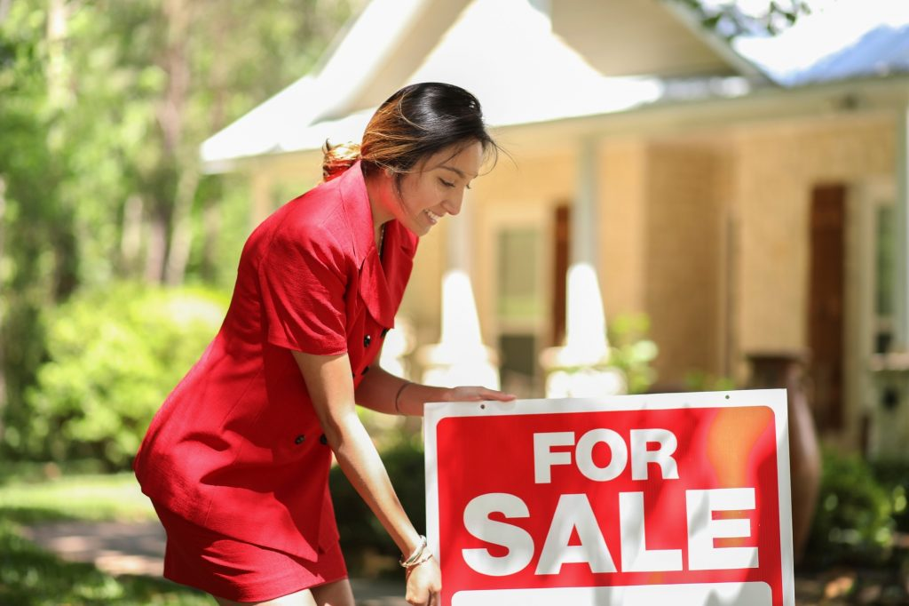 Real Estate agent holding the for sale sign