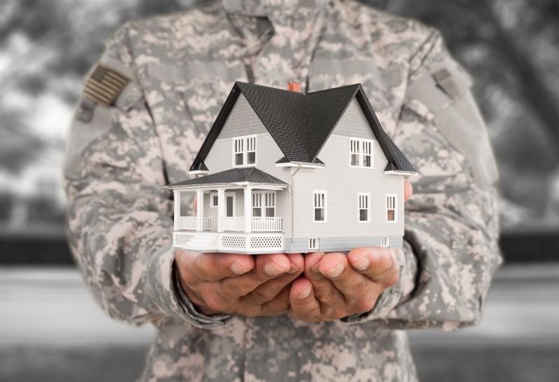 a man in military uniform holding a mini model house