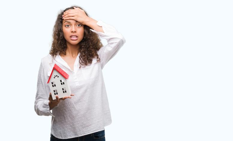 a woman holding aa mini model house